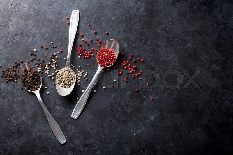 Stock image of 'Colorful peppercorn. Red, white and black pepper spices in spoons on stone table. Top view with copy space'