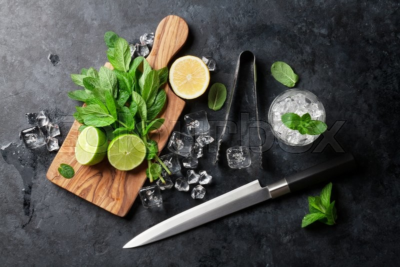 Stock image of 'Mojito cocktail making. Mint, lime, ice ingredients and bar utensils. Top view'