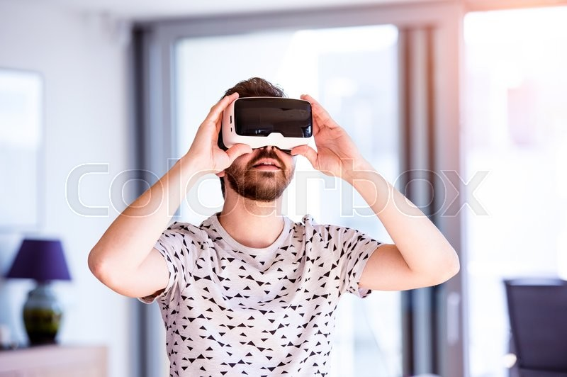 Stock image of 'Young hipster man wearing virtual reality goggles, standing in living room'