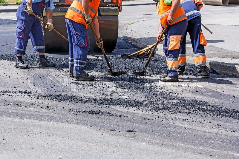 Stock image of 'Workers on Asphalting paver machine during Road street repairing works'