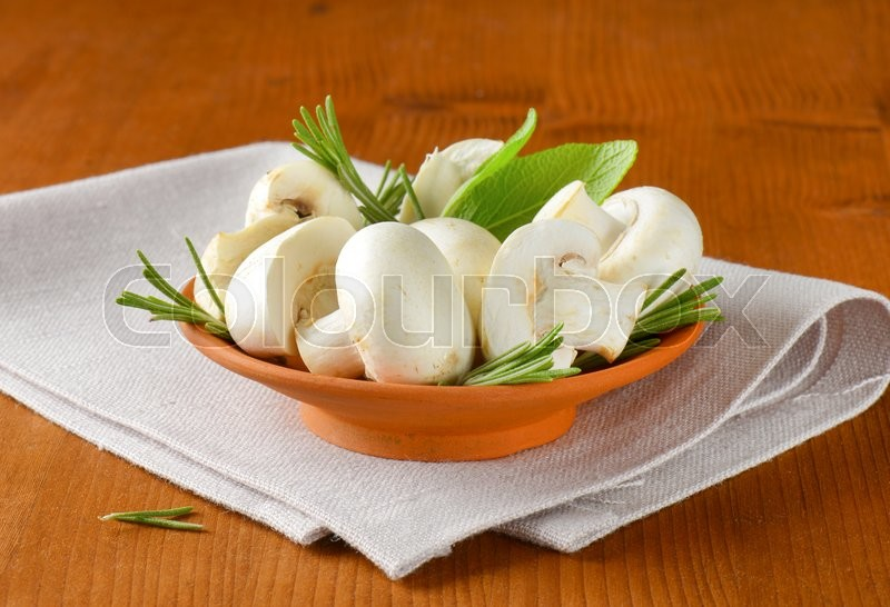 Stock image of 'Fresh button mushrooms and culinary herbs in terracotta bowl'
