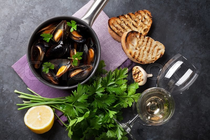 Stock image of 'Mussels in copper pot and white wine on stone table. Top view'