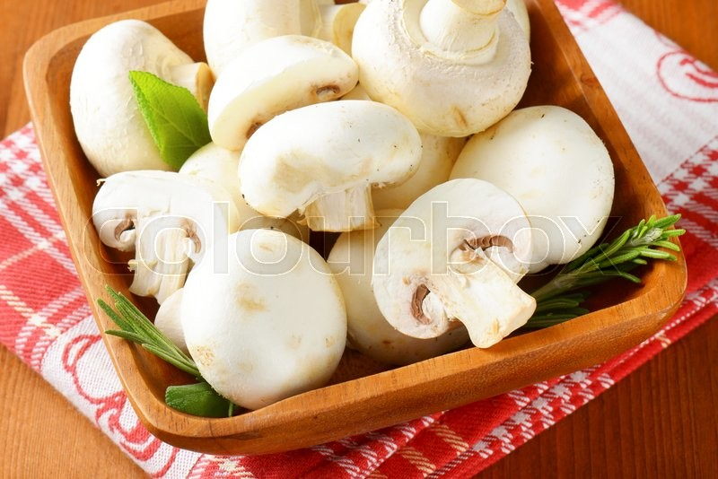 Stock image of 'Fresh button mushrooms in square wooden bowl'