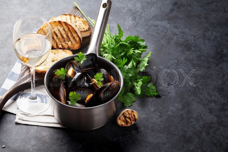 Stock image of 'Mussels in copper pot and white wine on stone table. View with copy space'