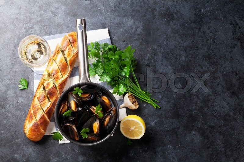 Stock image of 'Mussels in copper pot and white wine on stone table. Top view with copy space'