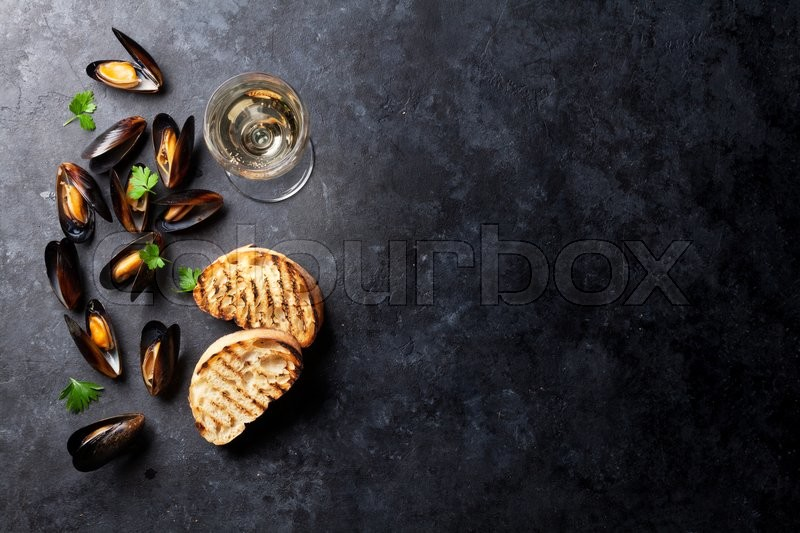 Stock image of 'Mussels, bread toasts and white wine on stone table. View with copy space'