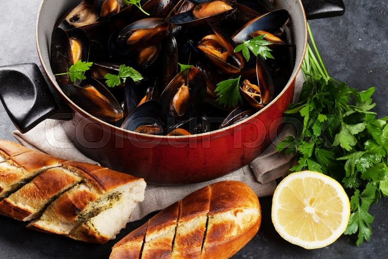Stock image of 'Mussels and homemade bread on stone table'