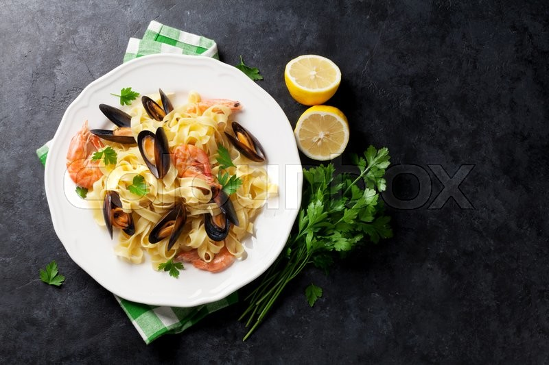 Stock image of 'Pasta with seafood on stone table. Mussels and prawns. Top view with copy space'