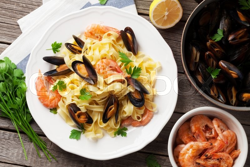Stock image of 'Pasta with seafood on wooden table. Mussels and prawns. Top view'