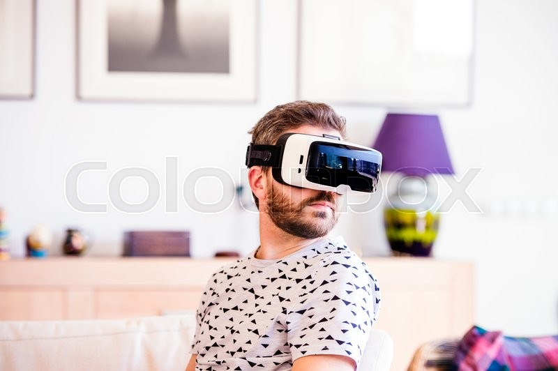 Stock image of 'Young hipster man wearing virtual reality goggles, sitting in living room'