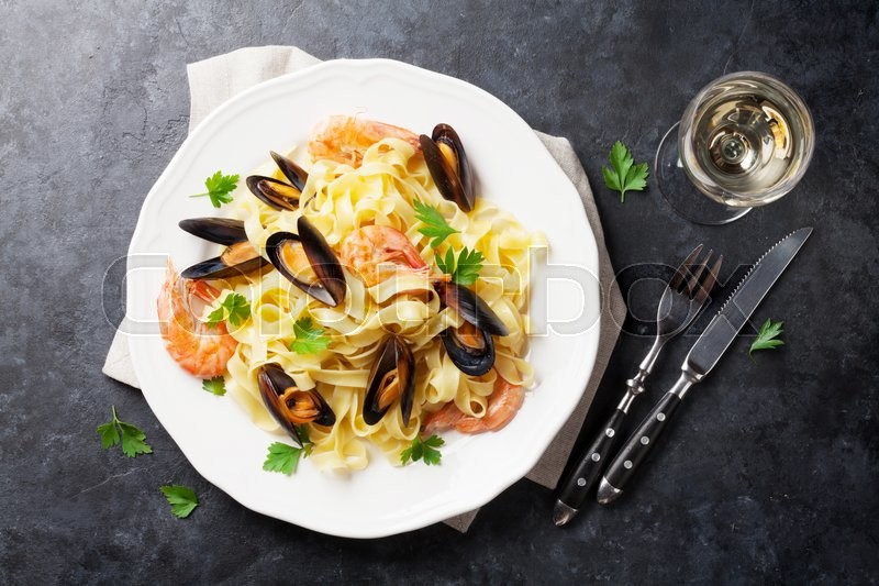 Stock image of 'Pasta with seafood and white wine on stone table. Mussels and prawns. Top view'