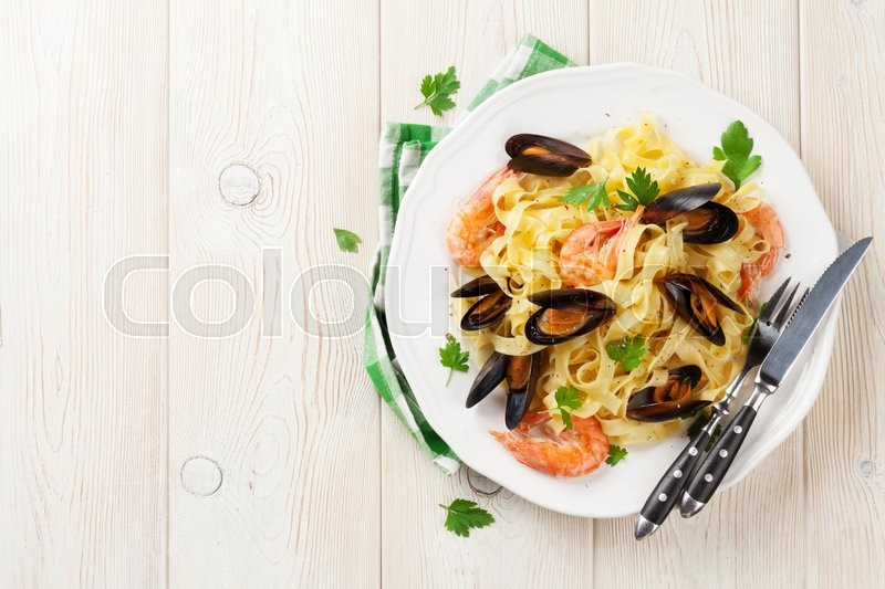 Stock image of 'Pasta with seafood on wooden table. Mussels and prawns. Top view with copy space'