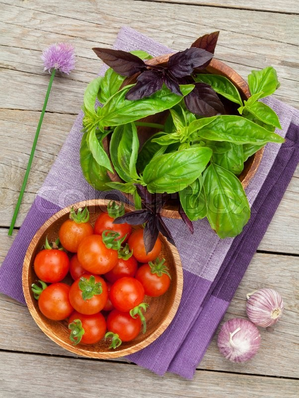 Stock image of 'Fresh farmers tomatoes and basil on wood table'