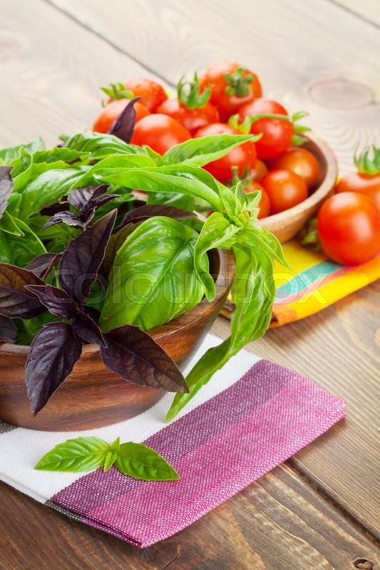 Stock image of 'Fresh farmers basil and tomatoes on wood table'