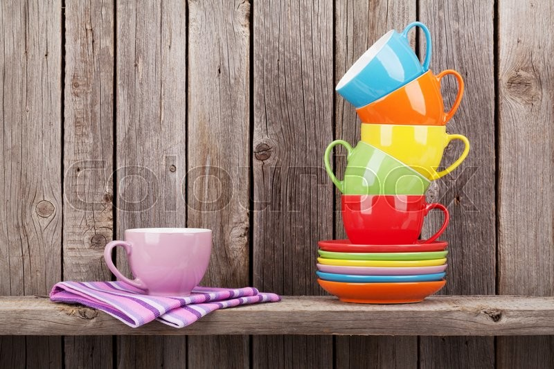 Stock image of 'Colorful coffee cups on shelf against rustic wooden wall with copy space'