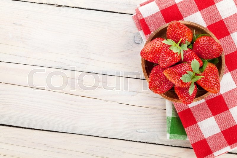 Stock image of 'Fresh ripe strawberry in bowl over wooden table background. Top view with copy space'