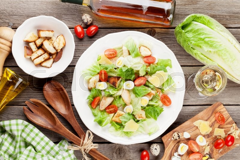 Stock image of 'Fresh healthy salad and white wine on wooden table. Top view'