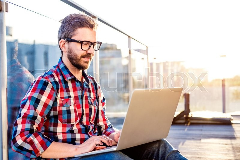 Stock image of 'Young businessman writing on a laptop computer, sitting on the balcony'