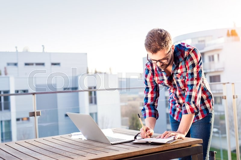 Stock image of 'Young businessman working on a laptop computer, standing on the balcony, writing into personal organizer'