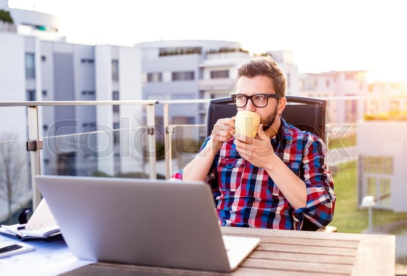 Stock image of 'Hipster businessman with laptop in checked shirt sitting on a balcony, holding a cup of coffee, relaxing'
