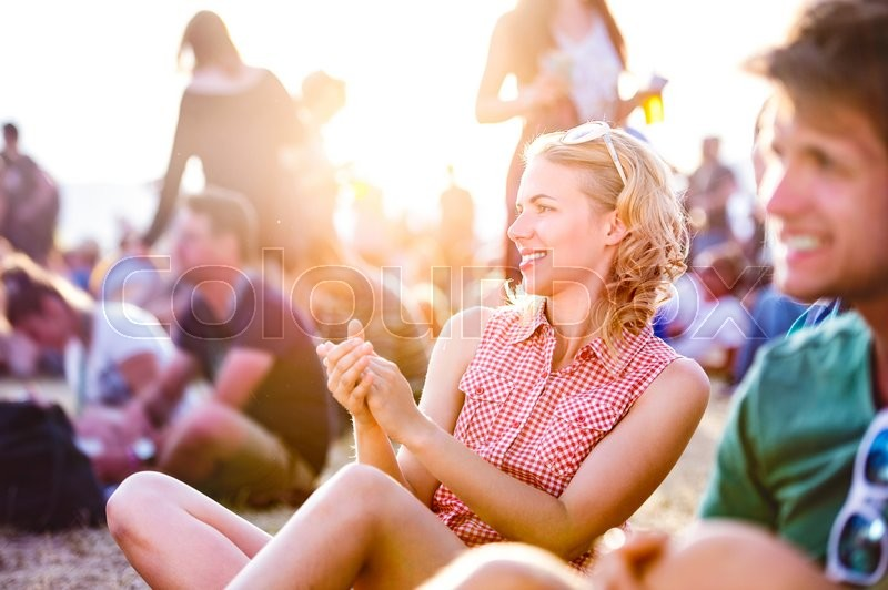 Stock image of 'Group of teenagers at summer music festival, sitting on the ground, teenage girl with blond curly hair, checked shirt'