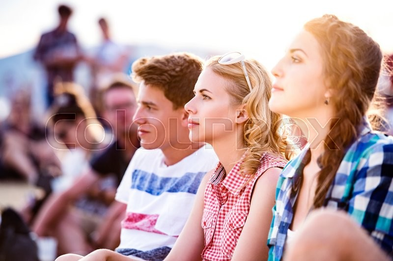Stock image of 'Group of teenage boys and girls at summer music festival, sitting on the ground'
