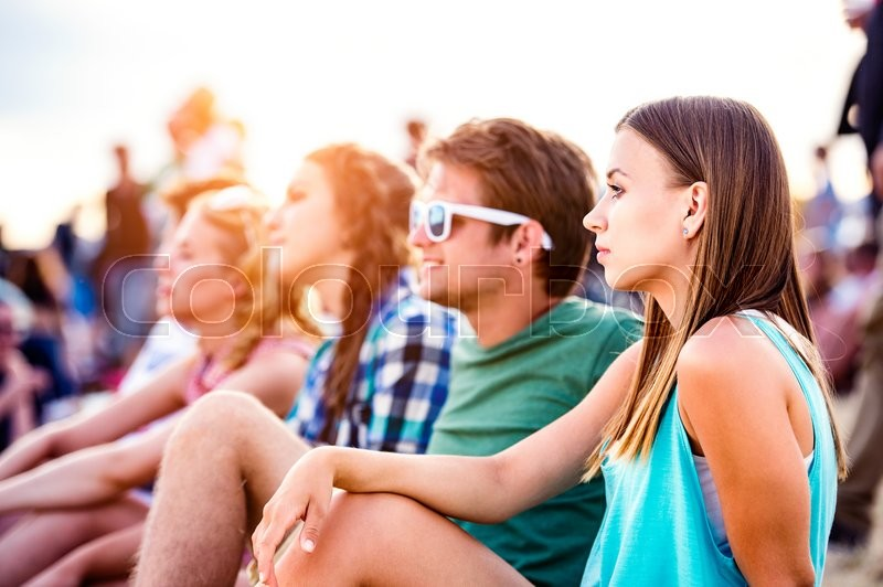 Stock image of 'Group of teenagers at summer music festival, sitting on the ground , hipster boy in green t-shirt'