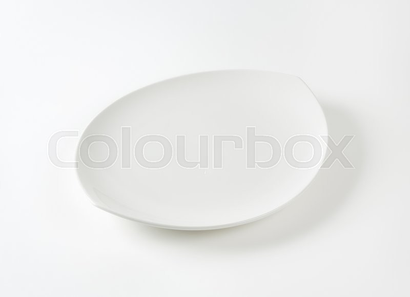 Stock image of 'Oval white porcelain plate with pointed ends'