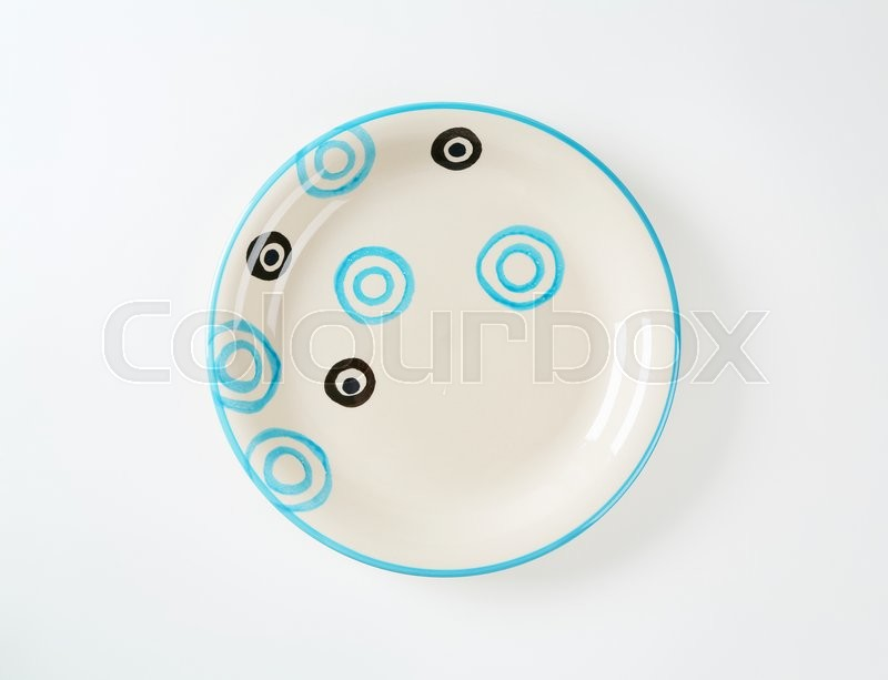 Stock image of 'White soup plate with black and blue circles'