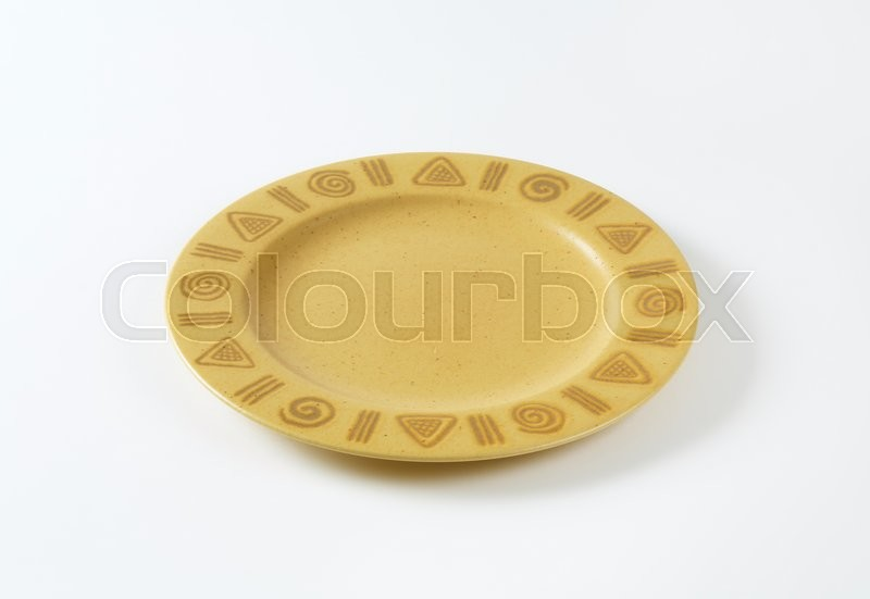 Stock image of 'Rustic ceramic plate decorated with symbols on the rim'