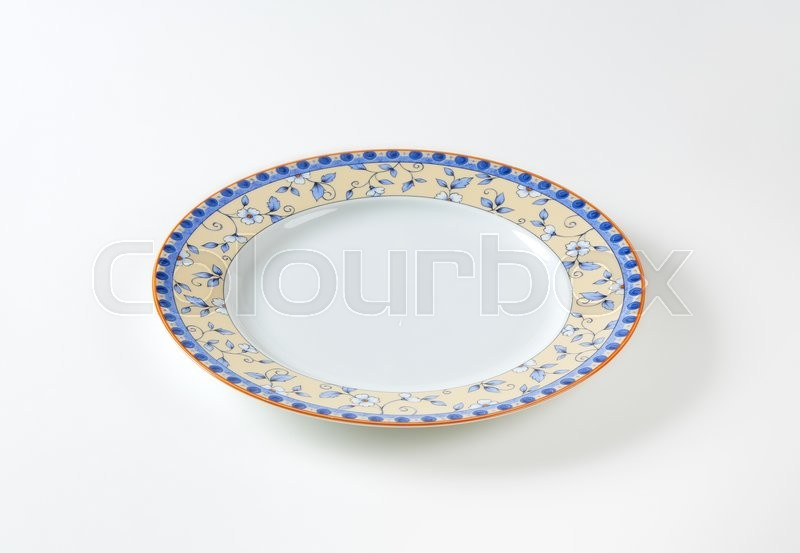 Stock image of 'Country style dinner plate with floral design border and brown trim'