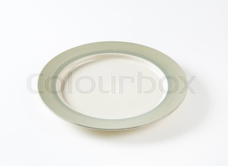 Stock image of 'Charger plate with wide grey rim decorated with a pattern of subtle rings'