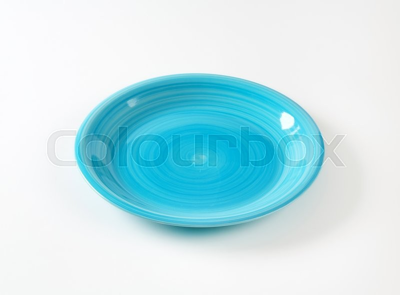 Stock image of 'Coup shaped ceramic plate with a blue color glaze'