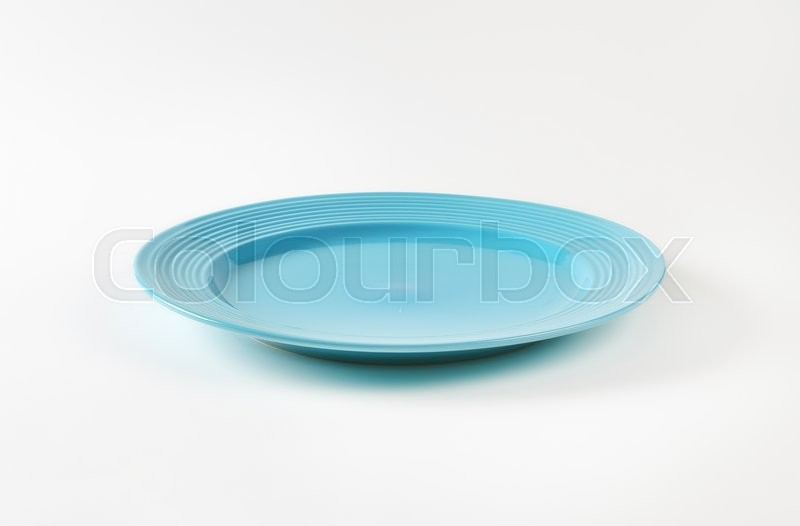 Stock image of 'Blue glazed dinner plate with embossed concentric rings on the edge'