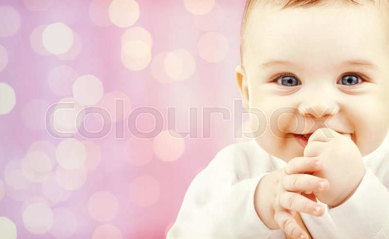 Stock image of 'children, holidays, people, infancy and age concept - happy baby over pink lights background'