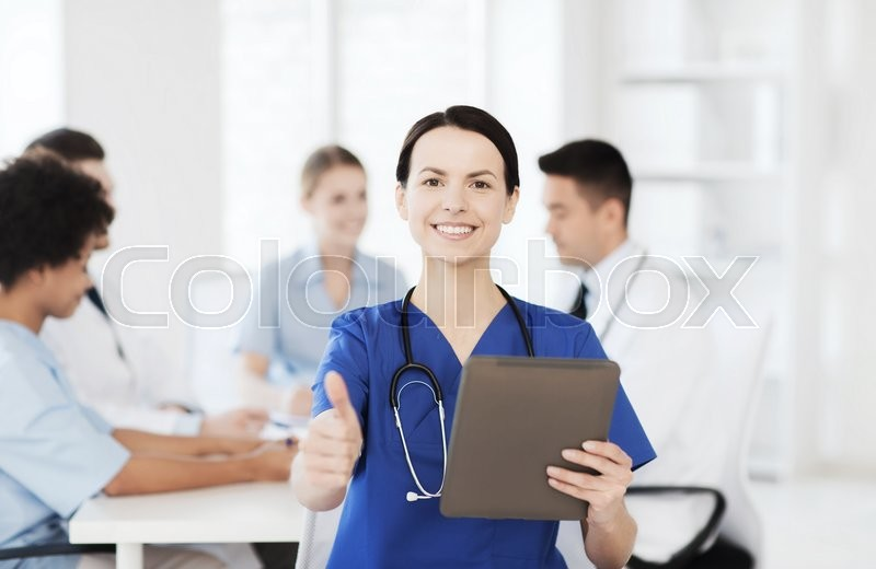 Stock image of 'clinic, profession, people and medicine concept - happy female doctor with tablet pc computer over group of medics meeting at hospital showing thumbs up gesture'