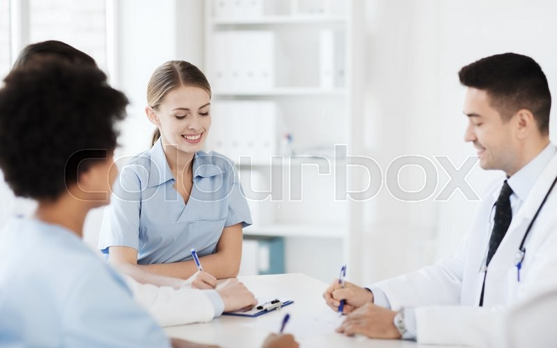 Stock image of 'hospital, profession, people and medicine concept - group of happy doctors meeting at medical office'