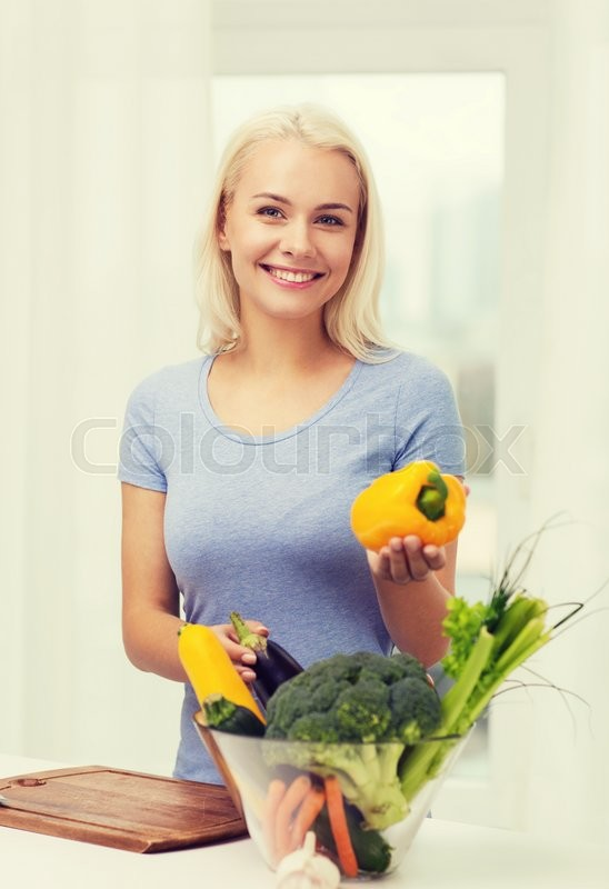 Stock image of 'healthy eating, cooking, vegetarian food, dieting and people concept - smiling young woman with bowl of vegetables at home'