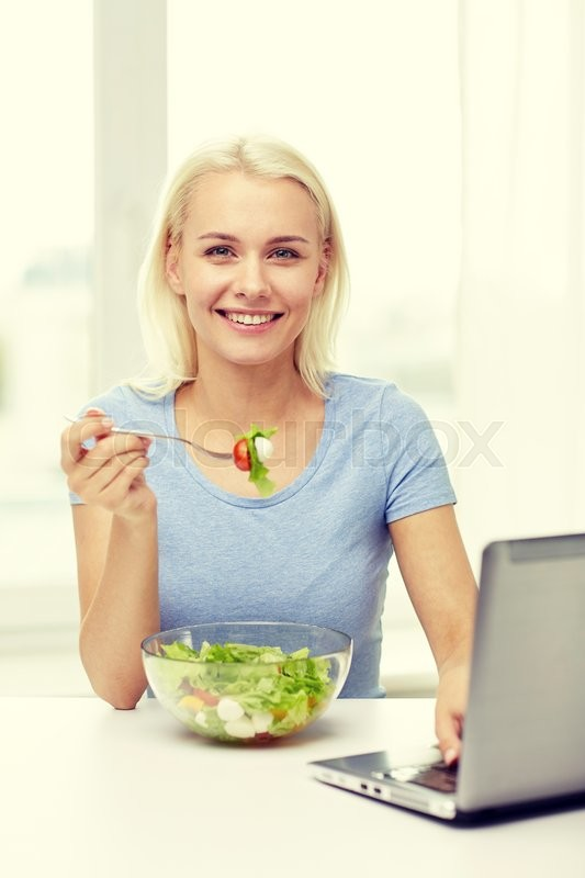Stock image of 'healthy eating, dieting, food, technology and people concept - smiling young woman with laptop computer eating vegetable salad at home'