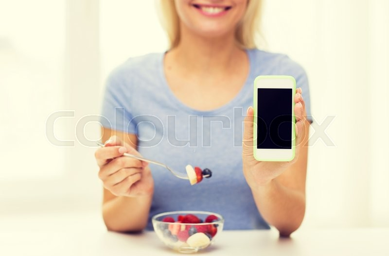 Stock image of 'healthy eating, dieting, technology, food and people concept - close up of young woman with smartphone eating fruit salad at home'
