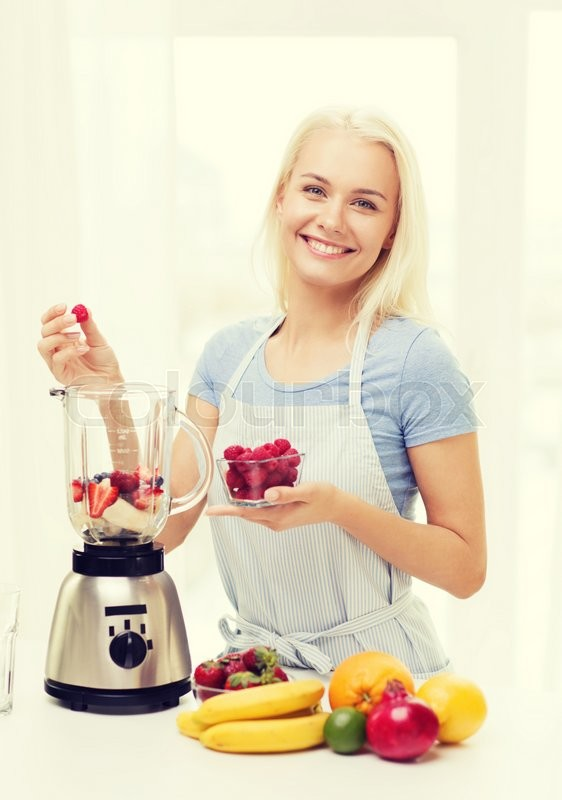 Stock image of 'healthy eating, cooking, vegetarian food, dieting and people concept - smiling young woman putting fruits and berries for fruit shake to blender shaker at home'