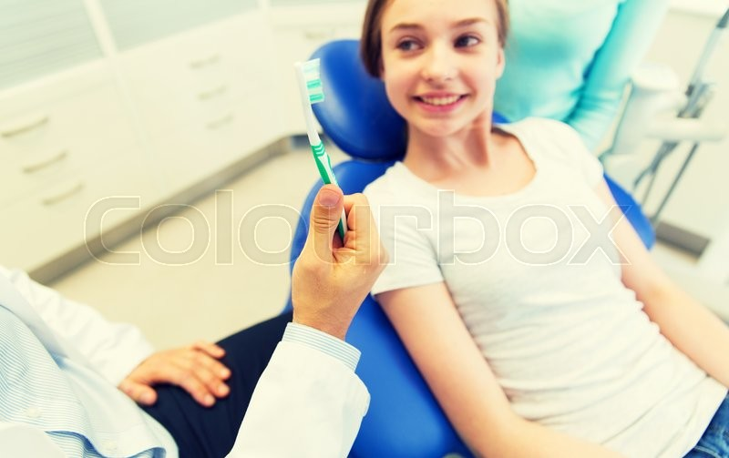 Stock image of 'people, medicine, stomatology and health care concept -close up of dentist hand holding toothbrush and patient girl at dental clinic office'