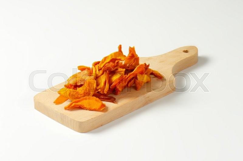 Stock image of 'Heap of dried mango slices on wooden cutting board'