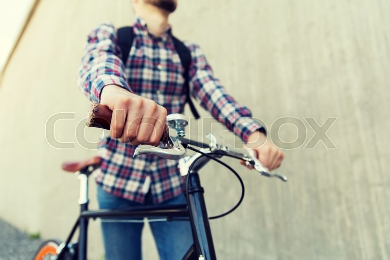 Stock image of 'people, travel, tourism, leisure and lifestyle - close up of young hipster man with fixed gear bike and backpack on city street'