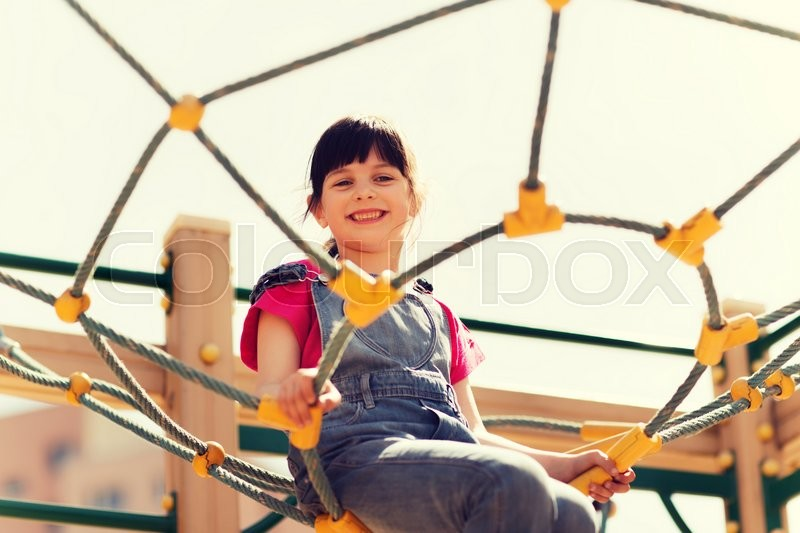 Stock image of 'summer, childhood, leisure and people concept - happy little girl on children playground climbing frame'