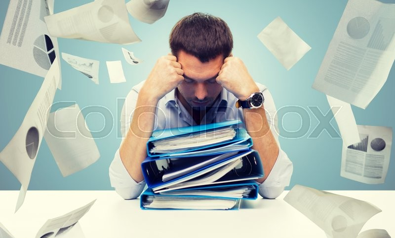 Stock image of 'business, people, deadline, stress and paperwork concept - sad businessman with stack of folders and falling papers over blue background'