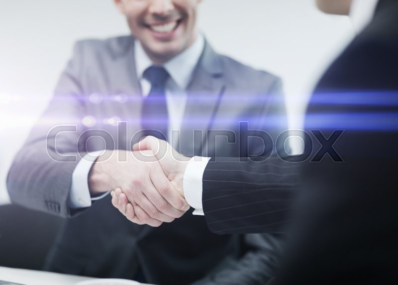 Stock image of 'businesss and office concept - two businessmen shaking hands in office'