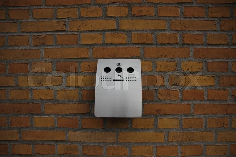 Stock image of 'Outdoor Grey Steel Ashtray mounted on Yellow Brick Wall'