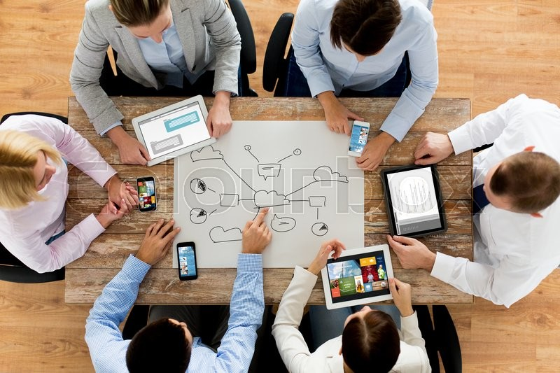 Stock image of 'business, people, technology, cloud computing and team work concept - close up of creative team with smartphones and tablet pc computers sitting at table in office'