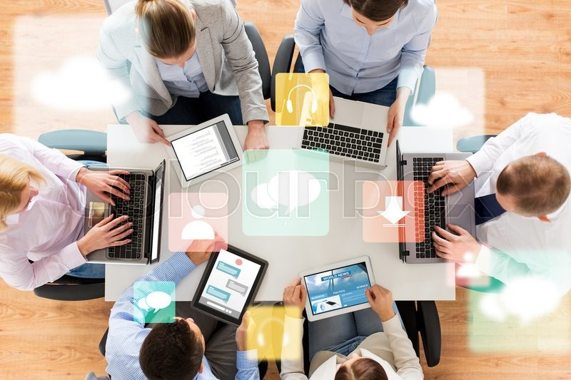 Stock image of 'business, people, media and technology concept - close up of creative team with laptop and tablet pc computers sitting at table in office'